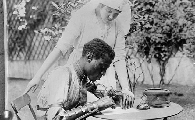 Сенегальский солдат из колониальных войск с анатомическими протезами вместо обеих рук восстанавливает навыки письма под наблюдением медсестры Американского Красного Креста.